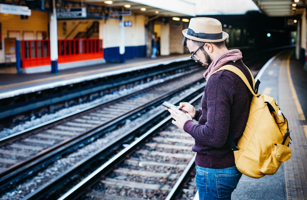 a man using his phone on a train station