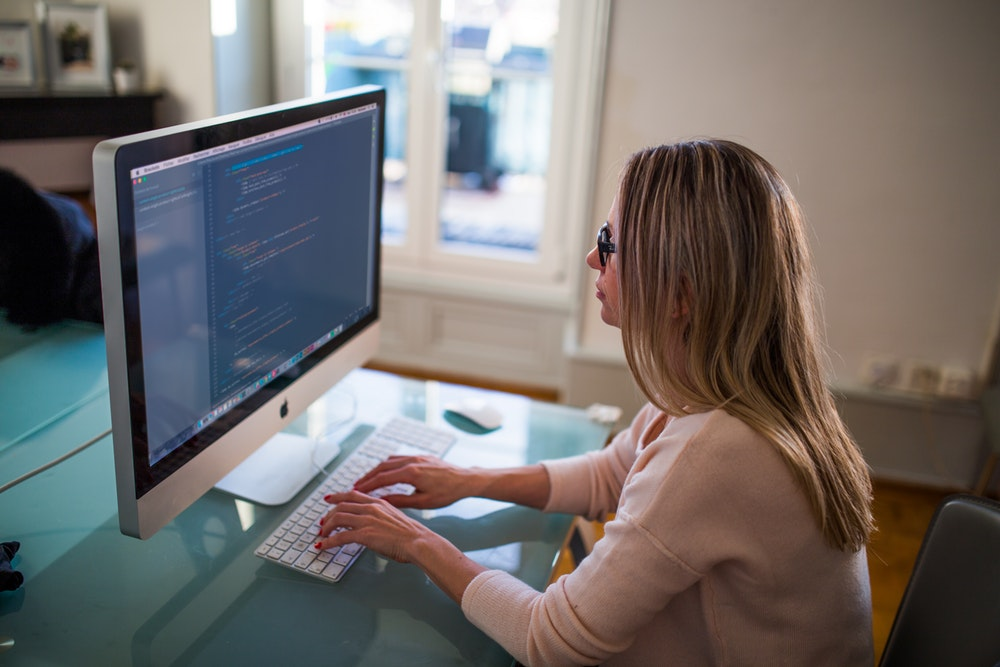 woman looking at lines of code on a Mac screen
