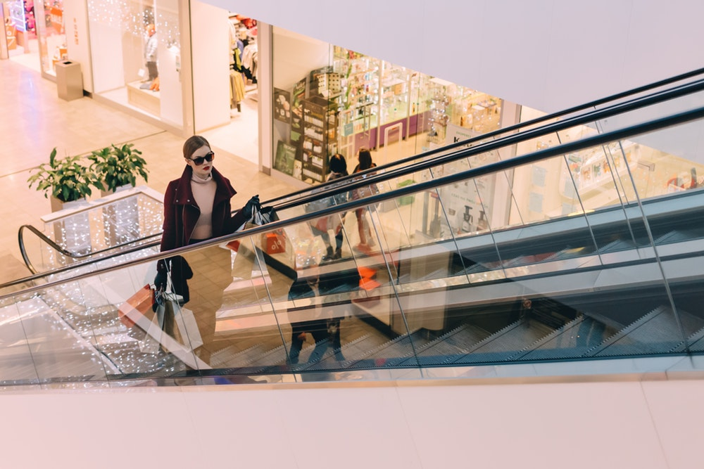 woman with shopping bags riding up the escalator in a mall