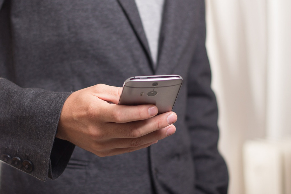 a man in a grey suit jacket looking at his phone