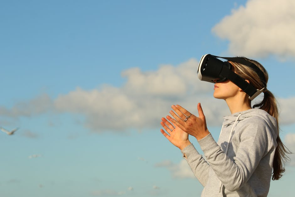 a woman wearing a VR headseat outdoors