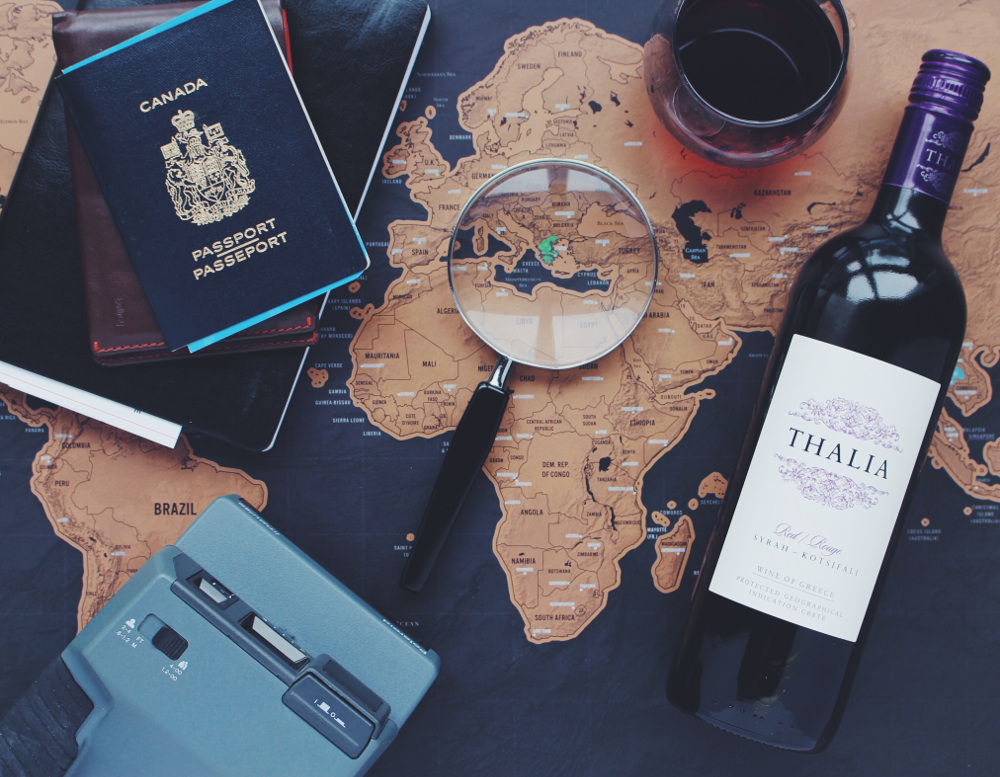 a map with a looking glass, glass of wine, an analogue camera and a passport on it