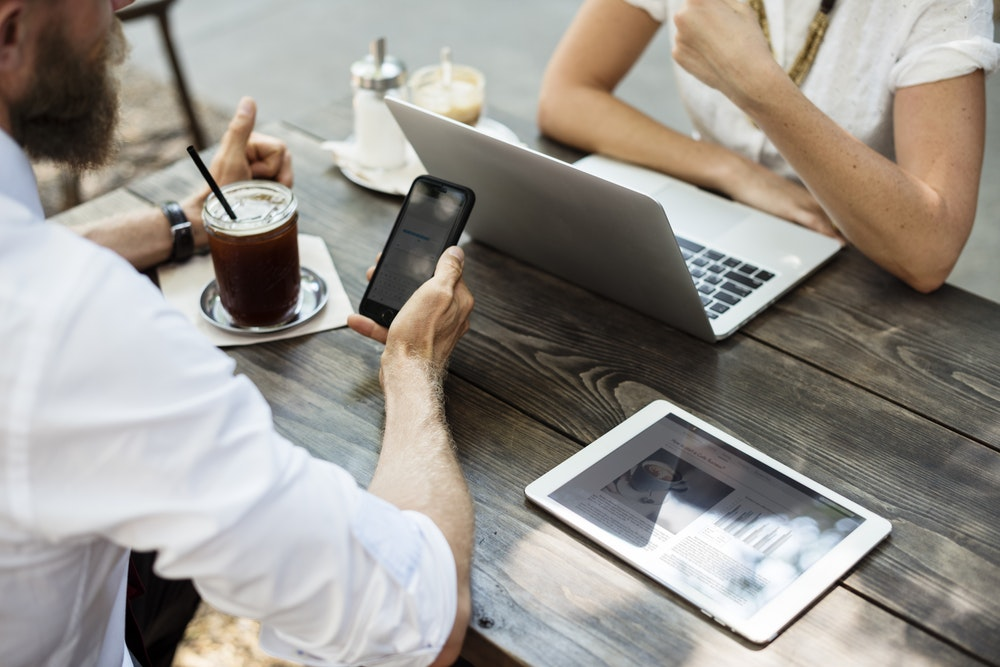 two people at a table, with their electronic devices, having a conversation over coffee
