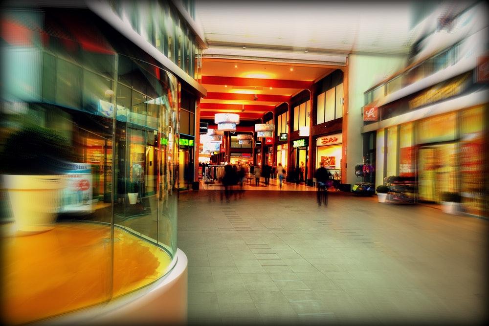 zdjęcie ludzi przechodzących alejką w centrum handlowym